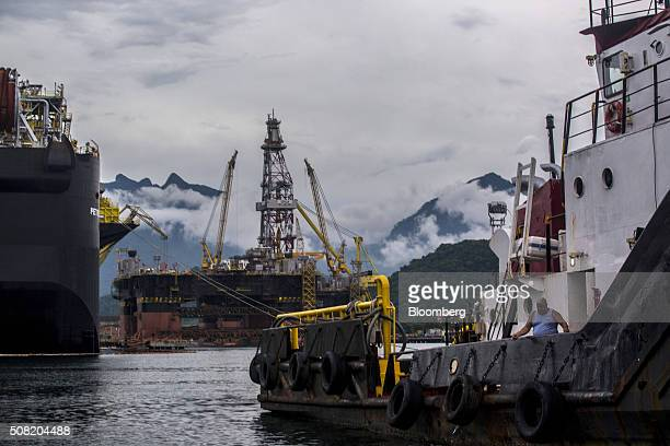 A worker fishes off the side of a tugboat right in front of a Petroleo Brasileiro SA Floating Production Storage and Offloading vessel center at a...
