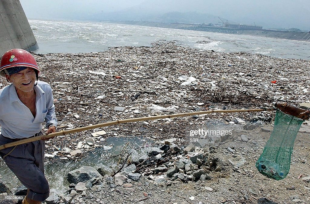 A worker fishes out rubbish near the Three Gorges dam in Yichang central China's Hubei province 04 June 2003 China's two biggest waterways face an...