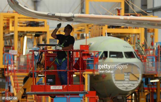 A worker fits a part to a wing of a partiallyfinished passenger plane of the A320 series in an assembly hall at the Airbus factory on July 14 2017 in...