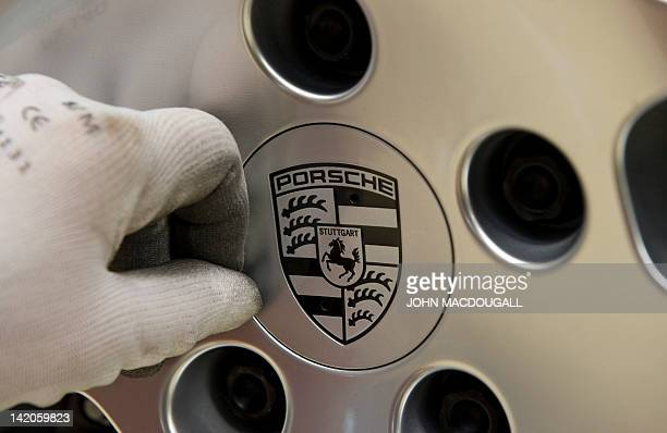 A worker fits a Porsche emblem in the hubcap of a Porsche Cayenne model on the production line of the Porsche plant in Leipzig eastern Germany March...