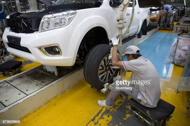 A worker fits a wheel onto a Nissan Motor Co Navara pickup truck on an assembly line at the company's plant in Samut Prakan Thailand on Tuesday April...