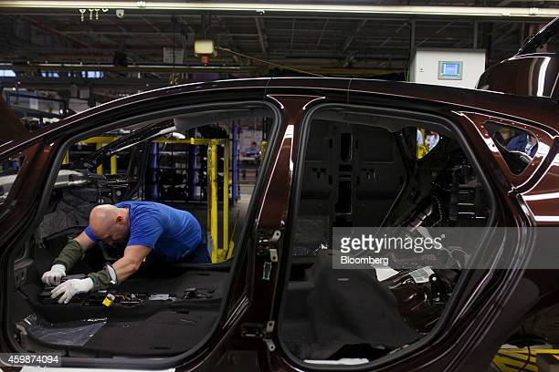 A worker fits an electronic assembly to the interior of an Opel Astra automobile as it passes along the production line at General Motors Co's Adam...