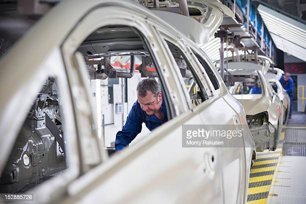 Worker fitting sound proofing to car in car factory