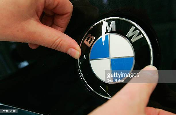 A worker fixes a BMW hood ornament onto a new BMW 3series car on the day of the plant's offical opening on May 13 2005 at the BMW factory in Leipzig...