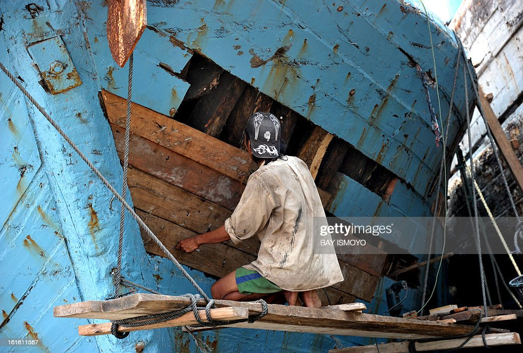 A worker fixes a broken traditional wooden cargo ship at Jakarta's port of Sunda Kelapa in Jakarta on February 13, 2013. Indonesia's central bank kept its key interest rate steady at 5.75 percent for the 12th straight month as it looks to boost growth in Southeast Asia's biggest economy. AFP PHOTO / Bay ISMOYO