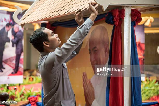 A worker fixes a tile on a roof housing a poster of Norodom Sihamoni the king of Cambodia and erected at the entrance of the 2017 World Economic...
