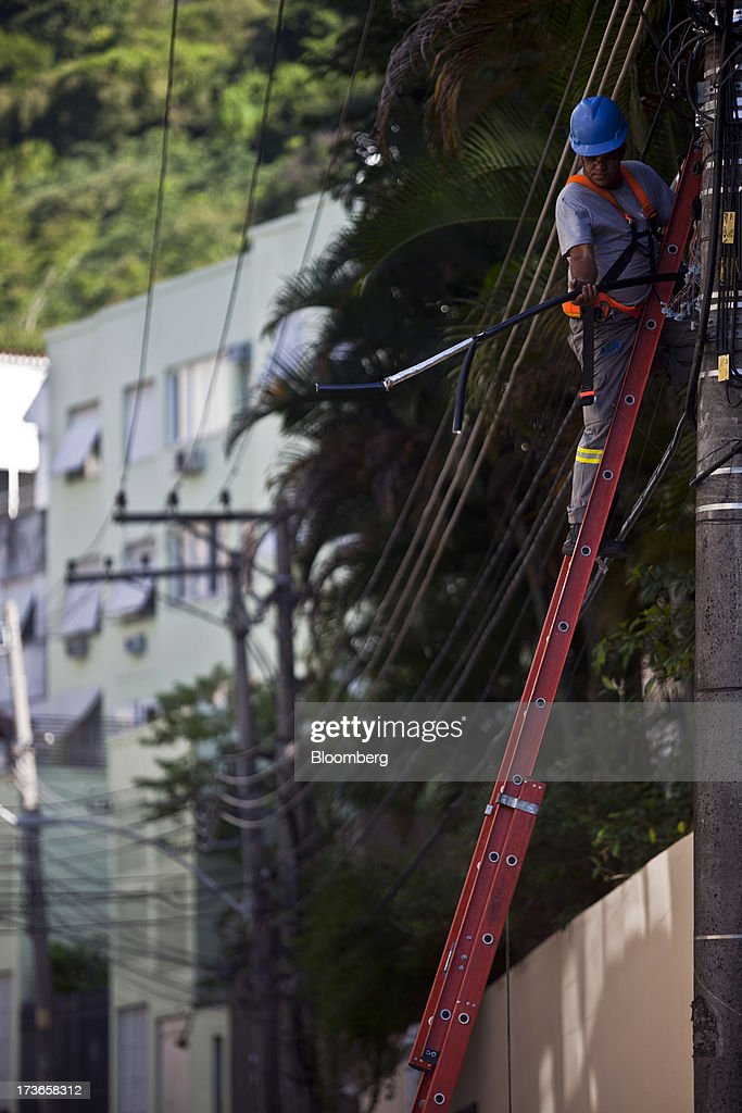 A worker fixes cables on a electricity pole in the Laranjerias neighborhood in Rio de Janeiro, Brazil, on Monday, July 15, 2013. Energy developers in Brazil will bid for contracts to sell electricity Dec. 13 from plants due to go into operation in five years, including a 700-megawatt hydropower project in the Amazon. Photographer: Dado Galdieri/Bloomberg via Getty Images