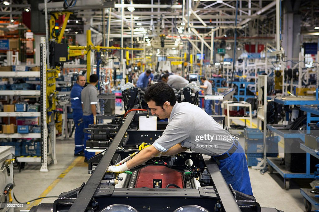 A worker fixes parts to the chassis of a Ford Cargo truck on the production line at Ford Otosan, the joint venture between Ford Motor Co.'s Ford Otomotiv Sanayi AS and Koc Holding AS, in Eskisehir, Turkey, on Monday, Nov. 18, 2014. Ford Otomotiv Sanayi AS chief executive officer Haydar Yenigun said in September Turkey is about to 'lose the diamond' which is light commercial vehicle production due to government policies such as tax hikes, ban on their lease, Dunya newspaper says. Photographer: Kerem Uzel/Bloomberg via Getty Images