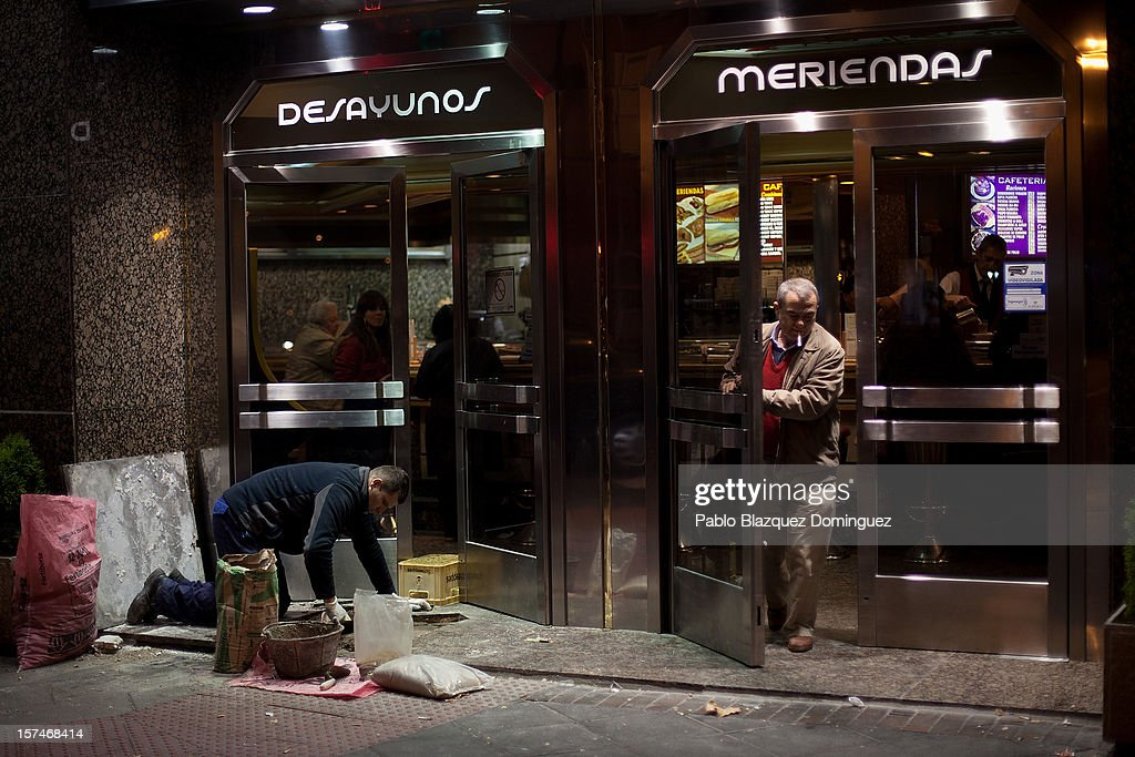 A worker fixes the exterior tiling of a tapas bar entrance in the evening as a man leaves on December 3, 2012 in Madrid, Spain. Spain has formally requested 39.5 billion euros of European funds to bailout a number of its struggling banks.