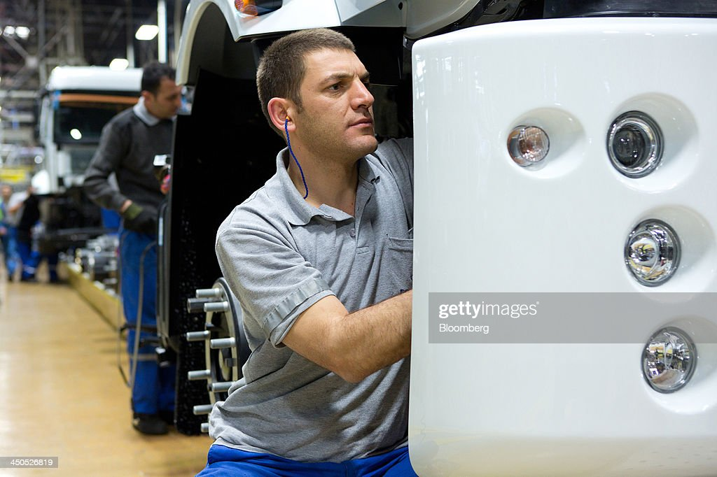 A worker fixes the headlight assembly to a Ford Cargo truck drivers cabin section on the production line at Ford Otosan, the joint venture between Ford Motor Co.'s Ford Otomotiv Sanayi AS and Koc Holding AS, in Eskisehir, Turkey, on Monday, Nov. 18, 2014. Ford Otomotiv Sanayi AS chief executive officer Haydar Yenigun said in September Turkey is about to 'lose the diamond' which is light commercial vehicle production due to government policies such as tax hikes, ban on their lease, Dunya newspaper says. Photographer: Kerem Uzel/Bloomberg via Getty Images