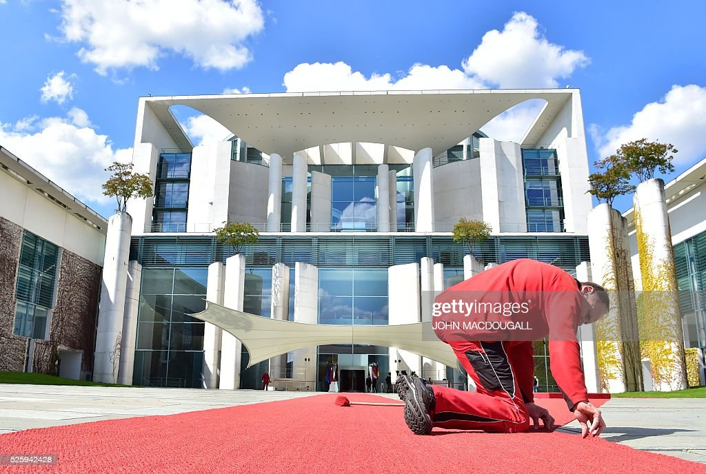 A worker fixes the red carpet in front of the chancellery ahead of a meeting of the German Chancellor with the Latvian Prime Minister in Berlin, on April 29, 2016. / AFP / John MACDOUGALL