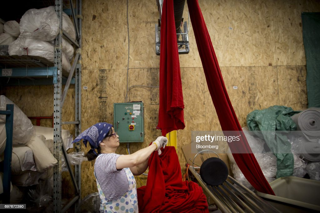 A worker folds fabric at the WS & Co. production facility in Toronto, Ontario, Canada, on Friday, June 9, 2017. Canada Day celebrates the anniversary of the creation of the Canadian Federation through the North America Act on July 1. Photographer: Brent Lewin/Bloomberg via Getty Images