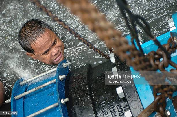 A worker for the Maynilad Water utilities install a valve on an excavated Manila's main water line to upgrade water distribution system 05 November...
