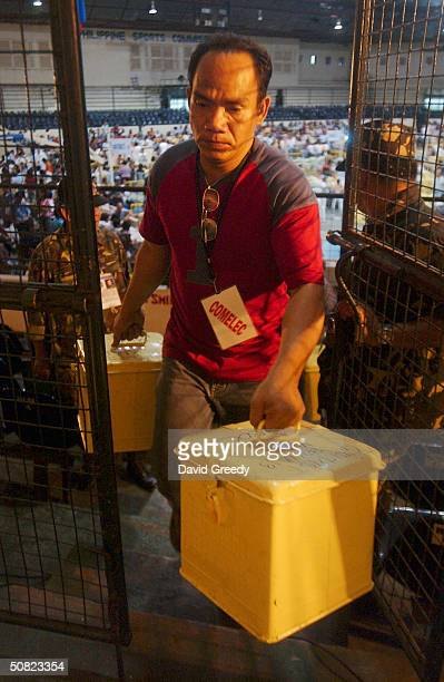 A worker for the Philippines Commision on Elections moves ballot boxes of sealed tally sheets to a secure location before official counting on May 11...