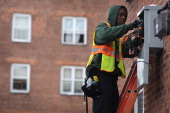 A worker for Time Warner Cable works to restore television reception to an apartment building on November 8 2012 in the Brooklyn borough of New York...