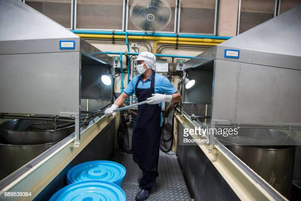 A worker fries garlic at the Nithi Foods Co factory in the San Pa Tong district of Chiang Mai Thailand on Tuesday May 23 2017 Thailand's consumer...