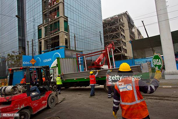 A worker from Cosapi SA holds a sign at the construction site of the Banco de la Nacion state bank headquarters building in the San Borja...