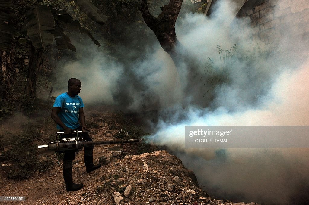 A worker from Haiti's Ministry of Public Health and Population sprays chemicals to exterminate mosquitoes in a neighborhood of Petion Ville in Port-au-Prince on May 21, 2014. A worker said the procedure is to help prevent chikungunya, dengue, malaria and filariose. AFP PHOTO / Hector RETAMAL