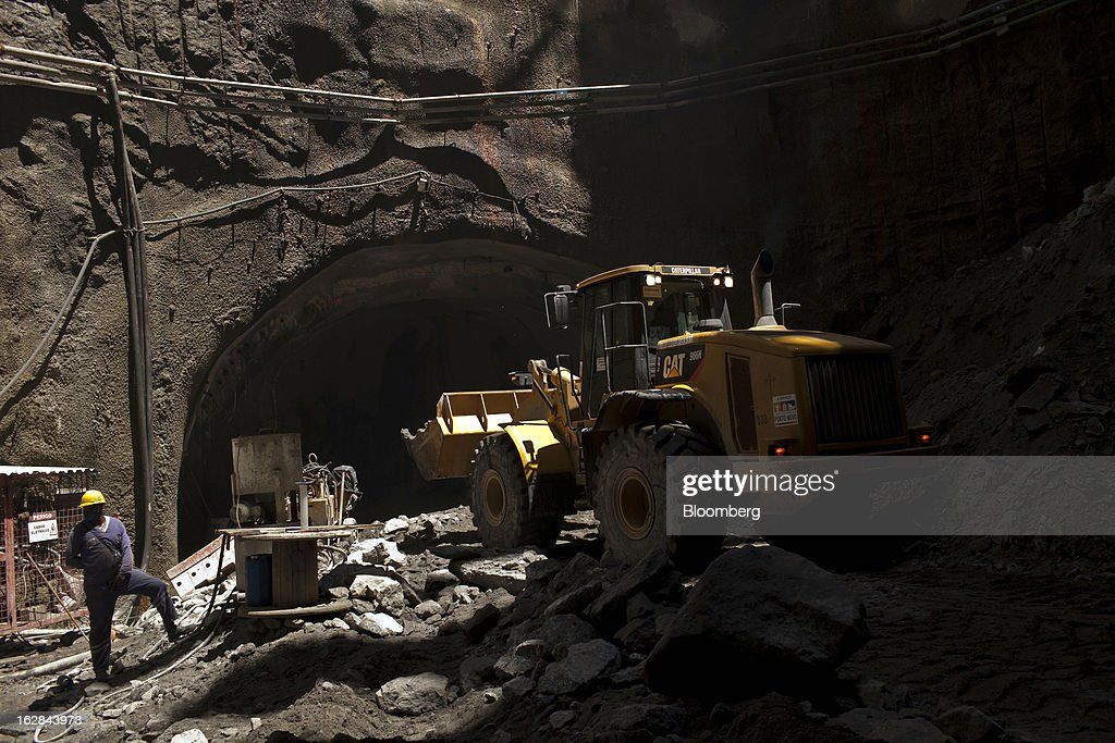 A worker from Novo Porto Consortium, a group funded by a mix of public and private agencies, looks on as a Caterpillar Inc. front loader removes debris during construction of the Binario tunnel in Rio de Janeiro, Brazil, on Thursday, Feb. 21, 2013. The tunnel is part of the $4 billion Porto Maravilha infrastructure project which aims to revitalize the the city's downtown and port area ahead of Brazil's hosting of the World Cup and Olympic Games. Photographer: Dado Galdieri/Bloomberg via Getty Images