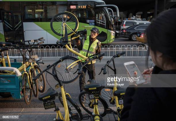 A worker from the bike share company Ofo unloads new bike shares during rush hour on March 27 2017 in Beijing China The popularity of bike shares has...