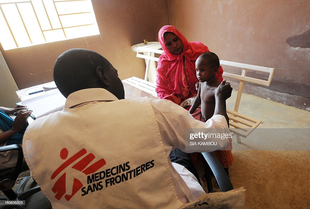 A worker from the NGO Doctors Without Borders speaks with a sick child in Gao, in the north of Mali, on February 4, 2013. Schools reopened today in Gao after the town was taken on January 26 by French and Malian forces from Islamists who had been occupying it for the last year. AFP PHOTO / SIA KAMBOU