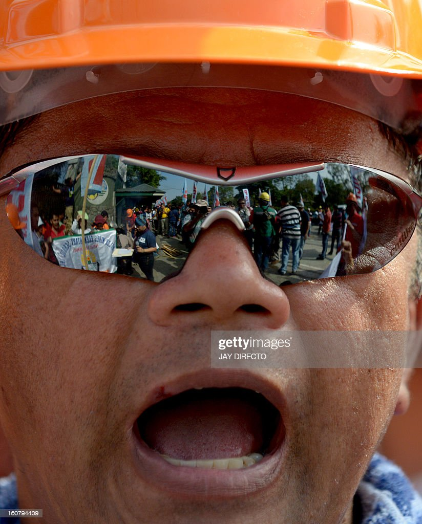 A worker from the Philippines' largest mining firm, Philex Mining, shout slogans with his colleagues outside the offices of the Mines and Geosciences Bureau in Manila February 6, 2013 as pigs (not pictured) are slaughtered as part of a religious sacrifice. The workers, who are from an indigineous tribe hoped the ceremonial offering would help convince the government to reopen the Padcal gold mine of the Philex Mining Corp. The company's main mining site in the northern mountain district of Padcal suffered a spill of mine waste or 'tailings' in August 2012 after the area was hit by two powerful typhoons, suspending operations at the mine since. AFP PHOTO / Jay DIRECTO
