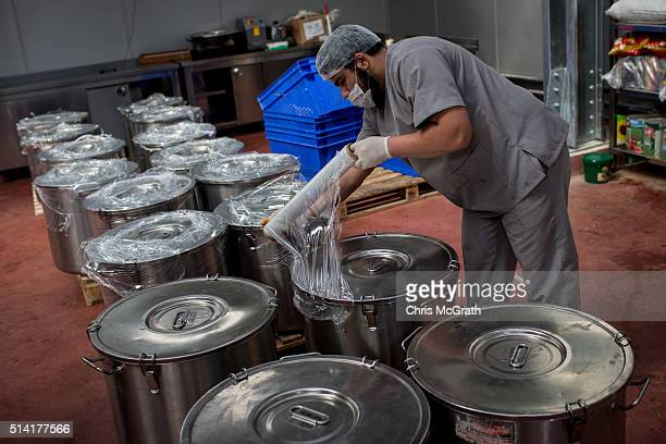 A worker from the Turkish Humanitarian Relief Foundation prepare to pack drums of hot bean soup for distribution to refugee camps across the Syrian...