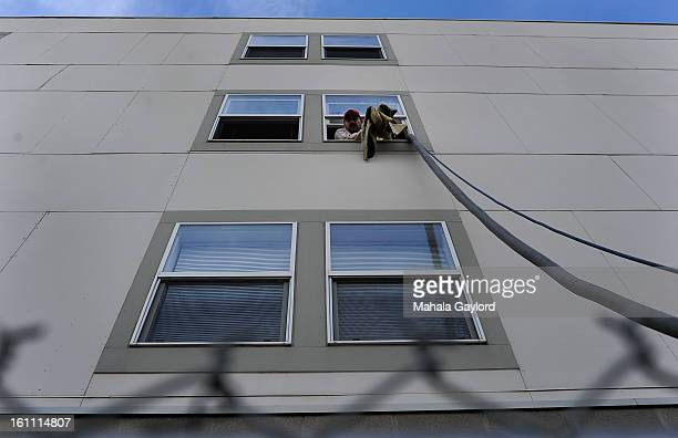 A worker from Venturi Clean shakes a water soaked cloth from the third story window of an apartment building on Park Avenue West while cleaning up...