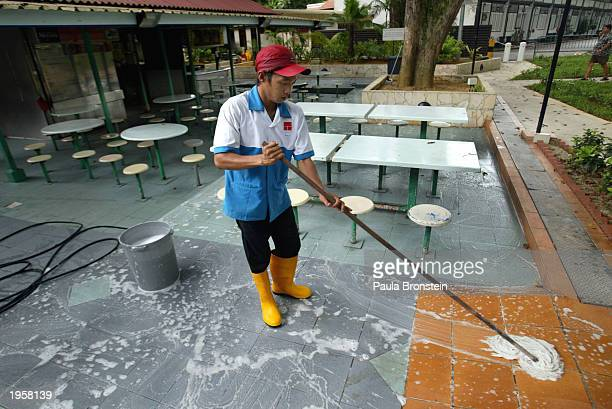 A worker fumigates and washes the popular open air Newton Food Center as a strong monsoonlike rain hits the area April 29 2003 in Singapore A massive...