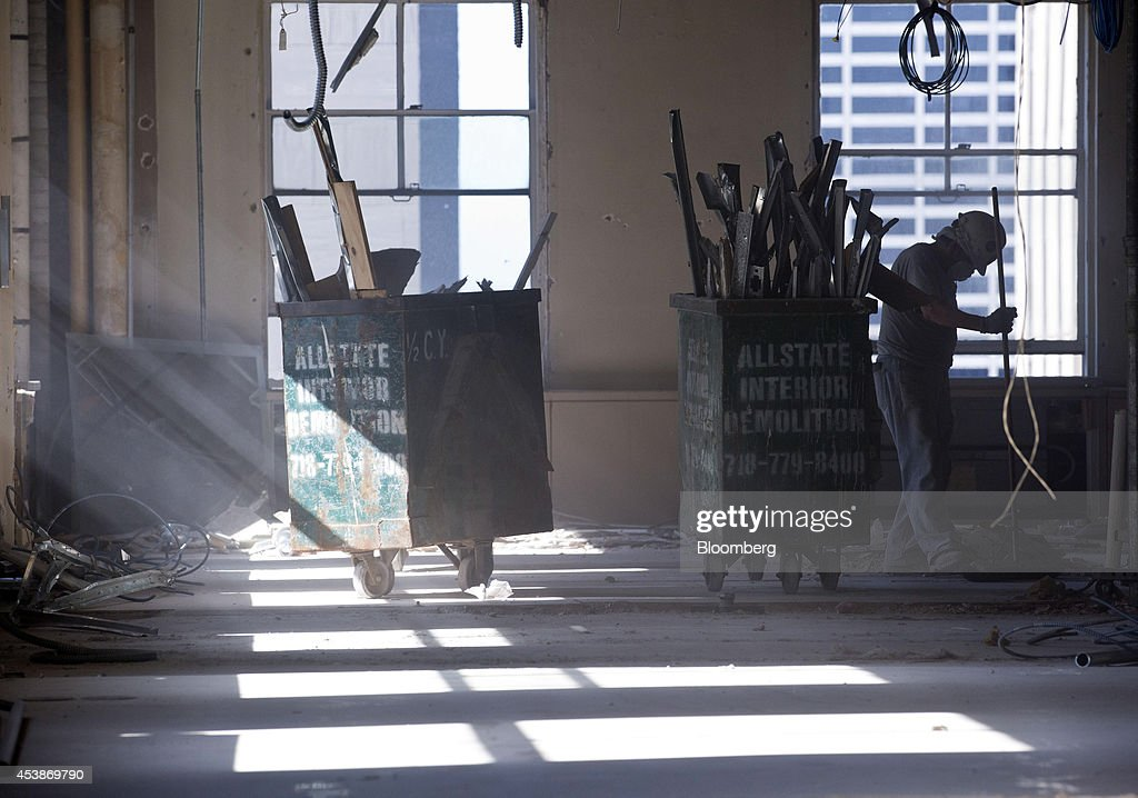 A worker gathers debris on the top floor at 75 Rockefeller Plaza during demolition ahead of renovations in New York, U.S., on Monday, Aug. 18, 2014. New landlord RXR Realty Corp. is upgrading the entire 630,000 square feet. The $150 million project includes raising office ceilings from 7.5 feet (2.3 meters) to 9 feet, and relocating mechanical equipment from the top floor to create new high-priced space, said Scott Rechler, RXRís chief executive officer. Photographer: Jin Lee/Bloomberg via Getty Images