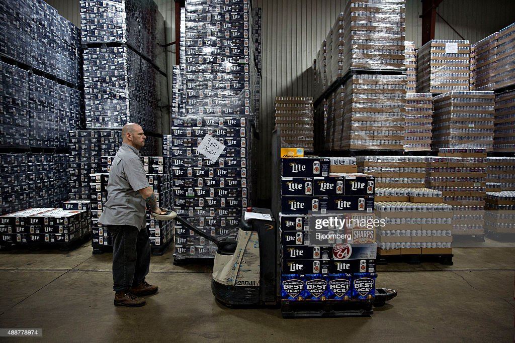 A worker gathers SABMiller brand beer for a customer order at the Baumgarten Distributing Co. warehouse in Peoria, Illinois, U.S., on Thursday, Sept. 17, 2015. Anheuser-Busch InBev NV unveiled plans to acquire SABMiller Plc yesterday, a deal that may cost the Budweiser brewer more than $100 billion as it seeks to unite the world's two biggest beermakers. Photographer: Daniel Acker/Bloomberg via Getty Images