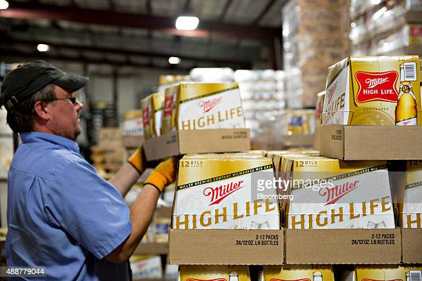 A worker gathers SABMiller Miller High Life brand beer for a customer order at the Baumgarten Distributing Co warehouse in Peoria Illinois US on...