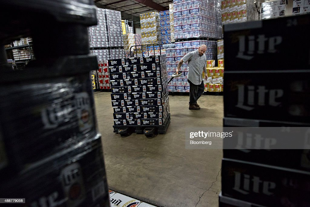 A worker gathers SABMiller Miller Lite brand beer for a customer order at the Baumgarten Distributing Co. warehouse in Peoria, Illinois, U.S., on Thursday, Sept. 17, 2015. Anheuser-Busch InBev NV unveiled plans to acquire SABMiller Plc yesterday, a deal that may cost the Budweiser brewer more than $100 billion as it seeks to unite the world's two biggest beermakers. Photographer: Daniel Acker/Bloomberg via Getty Images