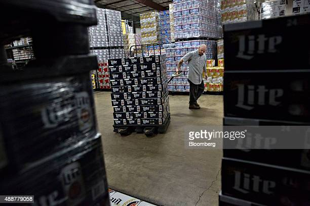 A worker gathers SABMiller Miller Lite brand beer for a customer order at the Baumgarten Distributing Co warehouse in Peoria Illinois US on Thursday...