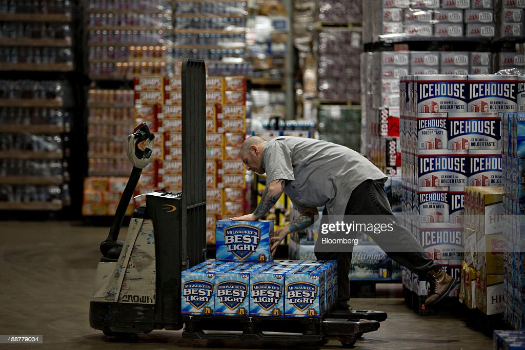 A worker gathers SABMiller Milwaukee's Best Light brand beer for a customer order at the Baumgarten Distributing Co. warehouse in Peoria, Illinois, U.S., on Thursday, Sept. 17, 2015. Anheuser-Busch InBev NV unveiled plans to acquire SABMiller Plc yesterday, a deal that may cost the Budweiser brewer more than $100 billion as it seeks to unite the world's two biggest beermakers. Photographer: Daniel Acker/Bloomberg via Getty Images