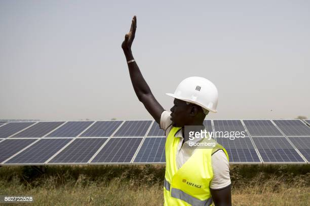 A worker gestures to colleagues during an inspection of photovoltaic solar panels at the Senergy Santhiou Mekhe PV solar plant in Thies Senegal on...