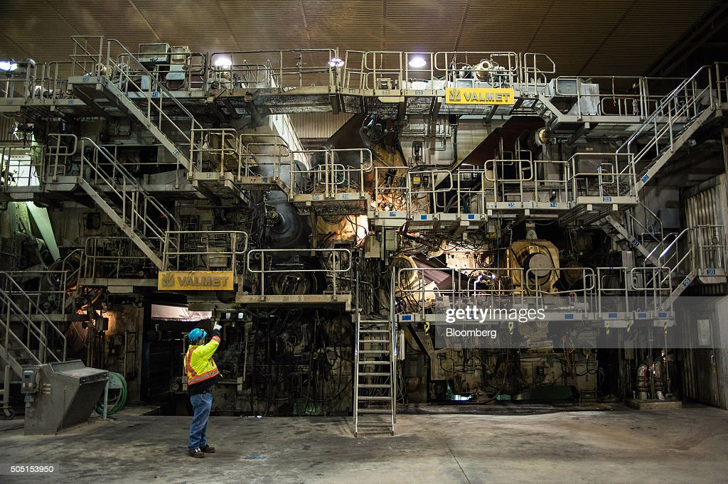 A worker gestures to the front end of the paper machine where the pulp enters before being processed into newsprint paper at the Resolute Forest...
