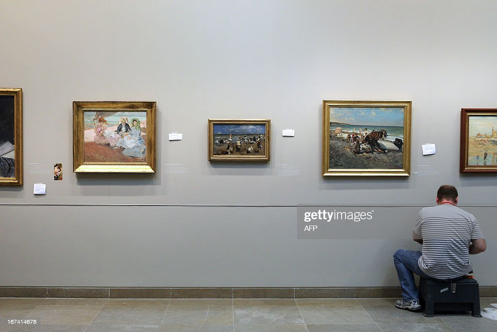 A worker gives the final touch to the painting captions on the wall, three days before the opening of 'Normandie Impressionniste' at Caen's fine arts museum, on April 24, 2013. The exhibition which takes place in Caen is one of the three most important, with the ones of Le Havre and Rouen, which are 'National interest' labelized. Caen's exhibition gathers 67 art paintings including 34 from abroad. This exhibition (in Rouen, Caen and Le Havre) begins on April 27 to September 29.