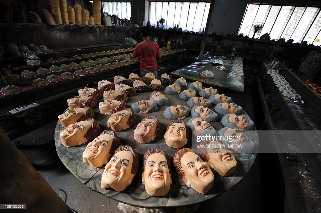 A worker gives the final touches to masks of President Dilma Rousseff and former President Luiz Inacio Lula da Silva at Condal carnival masks factory in Sao Goncalo, 35 km from dowtown Rio de Janeiro, Brazil, on February 3, 2012. AFP PHOTO/VANDERLEI ALMEIDA