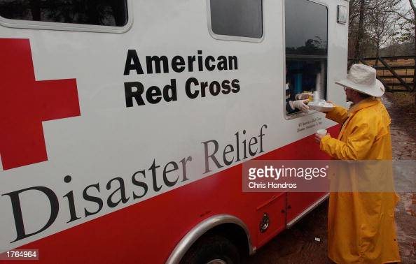 A worker grabs a meal of chili and coffee from a Red Cross truck during a break from search operations for debris of the space shuttle Columbia...