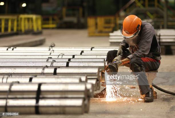 A worker grinds the edges of a bundle of finished steel rods at the Oskol Elektrometallurgical Plant steel mill operated by Metalloinvest Holding Co...