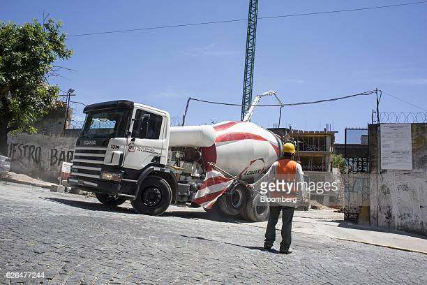A worker guides a concrete mixer inside the construction site for the Hornos 330 Master Office 3 building development in Buenos Aires Argentina on...