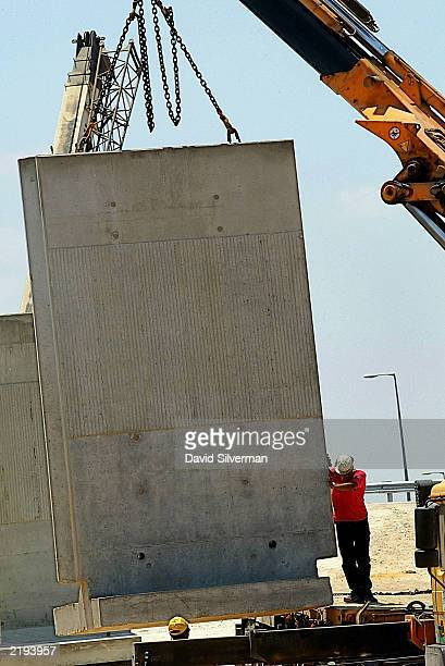 A worker guides a high concrete barrier into place July 24 2003 alongside the West Bank Palestinian town of Tulkarem Israel continues to build a...