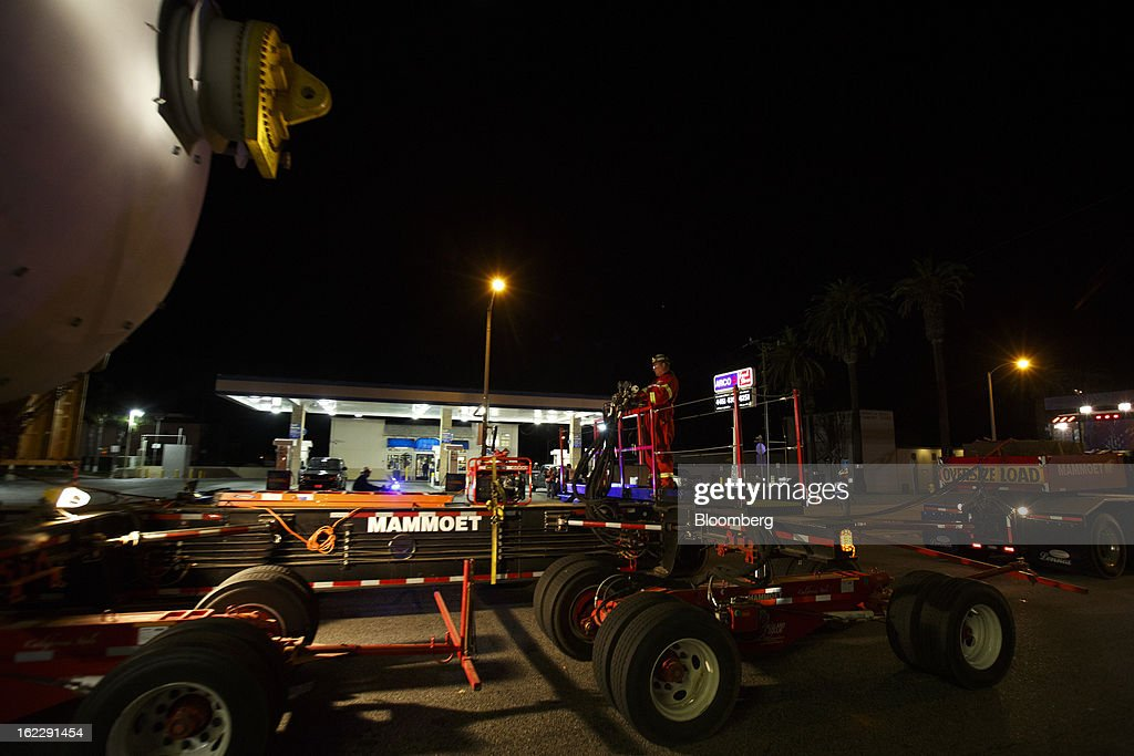 A worker guides a trailer manufactured by Mammoet Salvage BV as it transports a coke drum along the Pacific Coast Highway in Hermosa Beach, California, U.S., on Wednesday, Feb. 20, 2013. The drum, which measures over 100 feet long and weighs over 500,000 pounds, is one of six scheduled to be delivered to Chevron Corp.'s refinery in El Segundo. Photographer: Patrick Fallon/Bloomberg via Getty Images