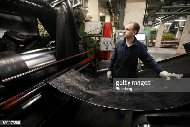 A worker guides a wide length of rubber used in the manufacture of tires at the Belshina JSC tire factory in Babruysk Belarus on Thursday March 16...