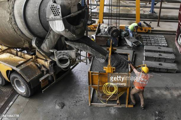 A worker guides concrete from a mixer truck into a kibble at the Mumbai Metro Rail Corp casting yard in Mumbai India on Monday Aug 28 2017 The...