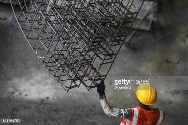 A worker guides the steel reinforcing frame of a precast concrete tunnel segment being maneuvered by crane to a mold at the Mumbai Metro Rail Corp...