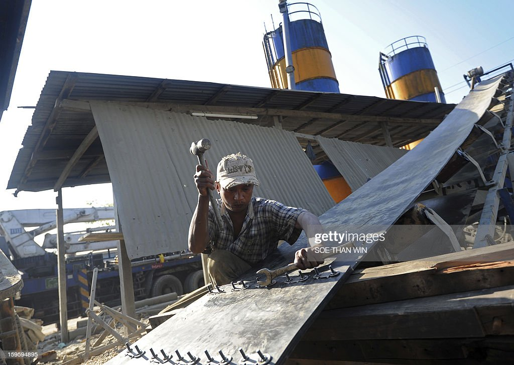 A worker hammers rivets onto a container belt at a pebble cleaning yard, used in concrete mix, in Yangon on January 17, 2013. Myanmar is one of the poorest countries in Asia after decades of economic mismanagement and isolation under army rule, but could become Asia's next economic engine if it enacts vast reforms, the IMF said in November of 2012. AFP PHOTO/ Soe Than WIN