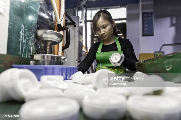 A worker handles a caster wheel at a workstation that will be replaced by an industrial robot at a factory operated by the Guangdong Shiyi Furniture...