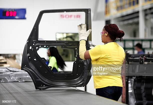 A worker handles a door that came out of the new $63 million press at the Fiat Chrysler Automobiles US Warren Stamping Plant January 22 2016 in...
